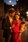 usmívající se muž objímající šťastnou přítelkyni držící kytici růží a přání s nápisem lásky a symbolem srdce