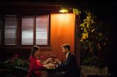 Seitenansicht eines eleganten Paares, das im Restaurant Gläser Rotwein trinkt