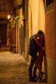 junges Paar umarmt und küsst sich, während es nachts in der Nähe der Mauer steht