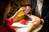 partial view of man clinking glasses of red wine with girlfriend while making marriage proposal