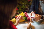 partial view of man presenting wedding ring to girlfriend while making marriage proposal