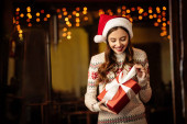 surprised young woman in warm sweater and santa hat opening gift box