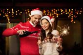 Fotografie fröhlicher Mann gießt Champagner in Glas glücklicher Freundin mit Wunderkerze