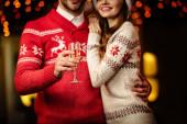 abgeschnittene Ansicht eines Mannes mit Champagnerglas, während er lächelnde Freundin umarmt