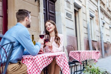 Cheerful young woman clinking glasses of red wine with boyfriend while sitting in street cafe stock vector