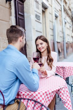 Happy girl clinking glasses of red wine with boyfriend while sitting in street cafe stock vector
