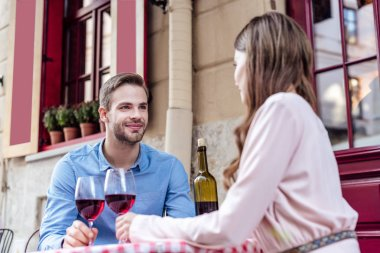 Happy young couple sitting in street cafe with glasses of red wine stock vector