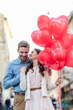 Smiling man embracing happy girlfriend holding red heart-shaped balloons on street stock vector