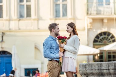 Handsome man presenting bouquet of roses to happy girlfriend on street stock vector