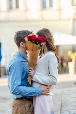 happy couple kissing while hiding behind bouquet of red roses