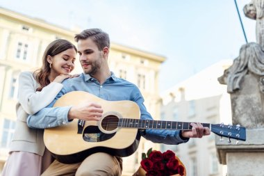 happy girl leaning on shoulder of boyfriend playing acoustic guitar on street