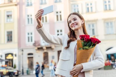 Cheerful girl holding bouquet of red roses and taking selfie on street stock vector