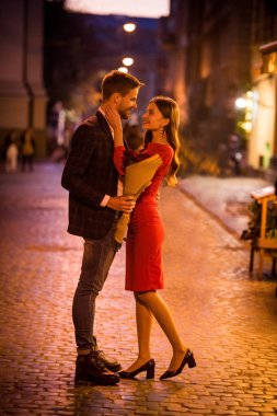 happy, elegant girl hugging boyfriend holding bouquet of red roses on night street