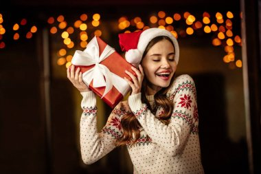 amazed young woman in warm sweater and santa hat holding gift box with closed eyes