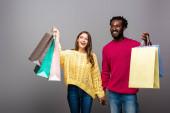šťastný mezirasový pár ve svetrech drží ruce a nákupní tašky na šedém pozadí