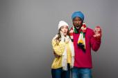 überrascht gemischtrassiges Paar im Winteroutfit, das sich auf grauem Hintergrund umarmt