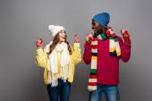 glückliches gemischtrassiges Paar im winterlichen Outfit jubelt auf grauem Hintergrund