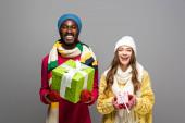 šťastný mezirasový pár v zimním oblečení držení dárky izolované na šedé