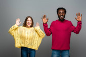 Photo excited interracial couple in knitted sweaters screaming and showing hands on grey background