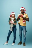 šokovaný mezirasový pár v Santa klobouky a šály držení hrnky s kakaem na modrém pozadí