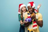 boldog lány télapó kalap és sál ajándékozás ajándék afro-amerikai barátja elszigetelt kék