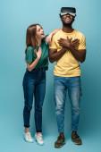 šťastná dívka stojící v blízkosti afrického amerického přítele ve vr sluchátka na modrém pozadí