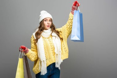 Shocked woman in winter outfit with shopping bags on grey background stock vector