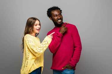 Smiling interracial couple in knitted sweaters pointing with fingers on grey background stock vector