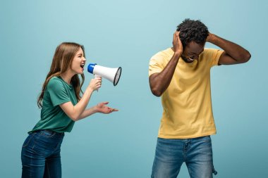 angry girl screaming in megaphone at african american boyfriend covering ears with hands on blue background