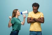 naštvaný dívka křičí v megafonu na africký americký přítel se zkříženými pažemi na modrém pozadí