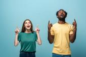 šokované mezirasový pár ukazuje s prsty nahoru na modrém pozadí