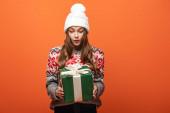 schockiertes Mädchen im Winteroutfit mit Geschenk auf orangefarbenem Hintergrund
