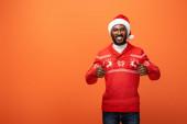 usmívající se africký Američan muž v Santa klobouk a vánoční svetr ukazující palce nahoru na oranžovém pozadí