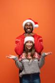 šťastný mezirasový pár v Santa klobouky a vánoční svetry na oranžovém pozadí
