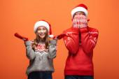 afro-amerikai férfi borító arc kezével közel boldog lány karácsonyi pulóver narancssárga háttér