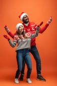 šťastný mezirasový pár v Santa klobouky, palčáky a vánoční svetry s natažené ruce na oranžovém pozadí