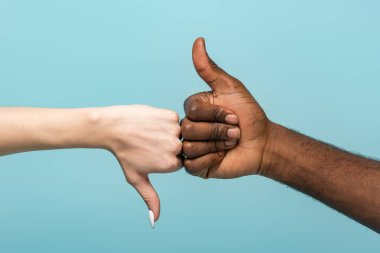 Cropped view of interracial couple showing thumbs up isolated on blue stock vector