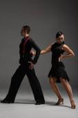 stílusos pár táncosok fekete ruhában tangót adó szürke háttér
