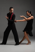 passionate couple of dancers in black clothing performing tango on grey background