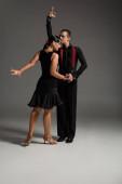 két fekete ruhás expresszív táncos tangózik szürke háttéren