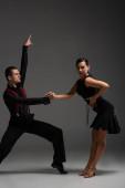 Ausdrucksstarkes Tanzpaar in schwarzer Kleidung, das Tango auf grauem Hintergrund aufführt