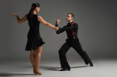 sensual couple of dancers in black clothing performing tango on grey background