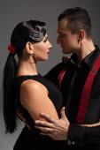 zwei leidenschaftliche Tänzer, die von Angesicht zu Angesicht Tango tanzen, isoliert auf grau