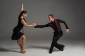 stílusos táncosok fekete ruhában nézik egymást, miközben táncolnak tangó szürke háttér