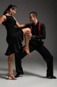 sensual dancer touching leg of partner while dancing tango on grey background