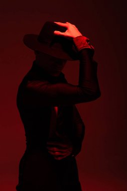 expressive dancer in black clothing and hat performing tango on dark background with red illumination