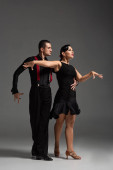 elegant couple of dancers in black clothing performing tango on grey background