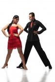 stylisches Tanzpaar, das Hände auf Hüften hält, während es Tango auf weißem Hintergrund vorführt