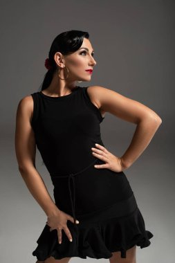 Attractive tango dancer in elegant black dress looking away on grey background stock vector
