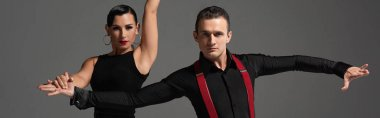 panoramic shot of stylish dancers looking at camera while performing tango isolated on grey